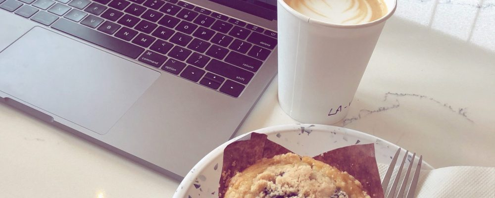 Laptop with graphic design software next to a muffin and coffee
